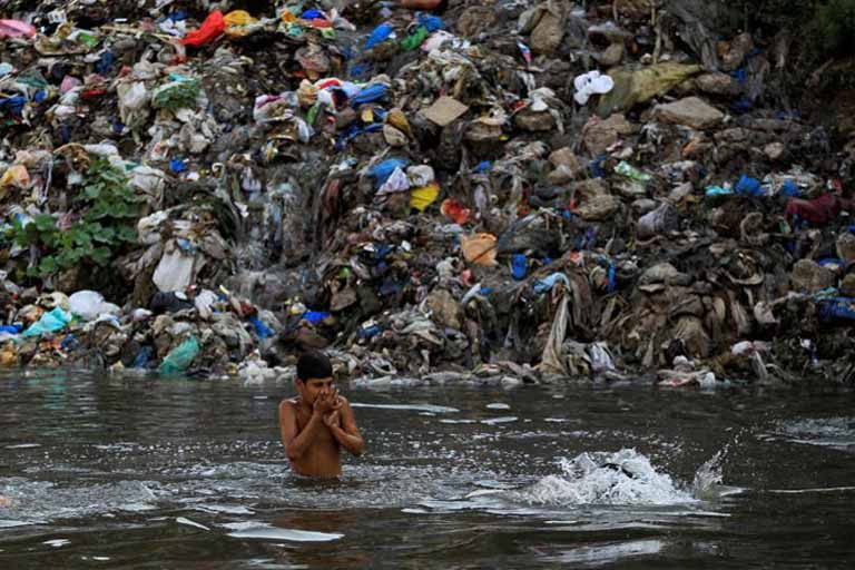 boy on water with garbage at the background