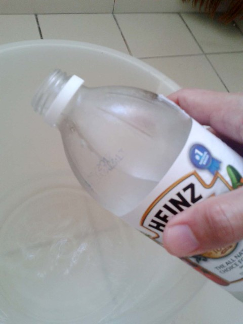white vinegar being poured into a small basin